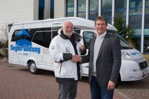 Klaus Dieter Böcker (Hobby-Geschäftsführer) übergibt Schlüssel des Hobby Premium Drive 70 GE an Hermann Hell (Chefredakteur Segler-Zeitung). © spothits/Hobby