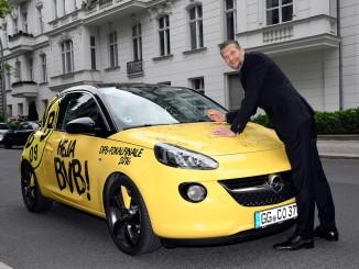 """Signierter Opel Adam wird versteigert. © spothits/Der signierte Opel Adam im BVB-Design wird zugunsten Stiftung """"leuchte auf"""" versteigert: Kampangenbotschafterin Bettina Zimmermann./Foto: Opel"""
